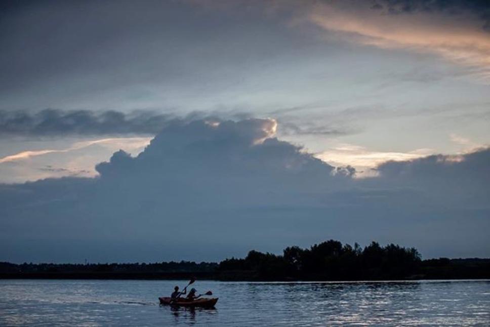 Zdjęcie kajakarzy na spokojny jeziorze. W tle las.